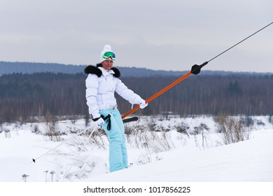 woman in a white jacket on a ski mountain resort rises on a lift