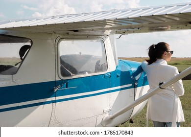 a woman in a white jacket stands near the plane