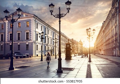 Woman in white jacket walking Malaya Konyushennaya  street with Lanterns and ol buildings in Saint Petersburg