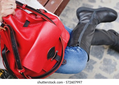 236195fee54 Woman in white knitted coat and skinny dark blue jeans with big leather red  bag in