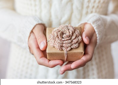Woman in white knitted sweater holding a present. Gift is packed in craft paper with hand made crocheted flower. Example of DIY ways to pack Christmas and other presents.