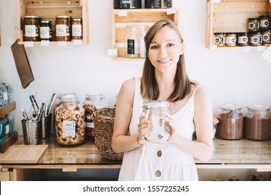 Woman in white linen dress with empty glass jar buying in sustainable plastic free grocery store. Girl with reusable cotton bag and wicker basket in zero waste shop. Minimalist low waste lifestyle