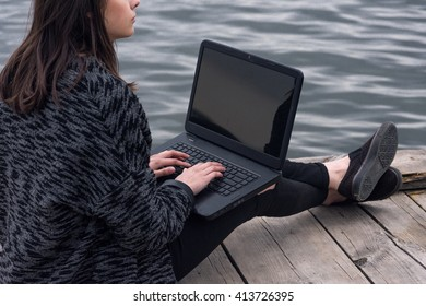 Woman in white looking at a laptop on pier
