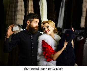 Woman in white mink fur coat and man looks at each other with smiling faces. Girl shopping and holds hanger with dark coat on. Macho holds card with furry coats on background. Couple shopping concept.