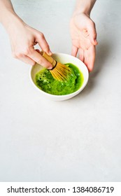Woman in white prepare Japanese green Matcha tea by whipping it in a bowl with a bamboo Chasen whisk on a white background with copy space.