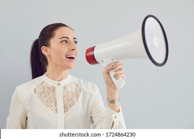 A woman in a white shirt in a bullhorn on a gray background.