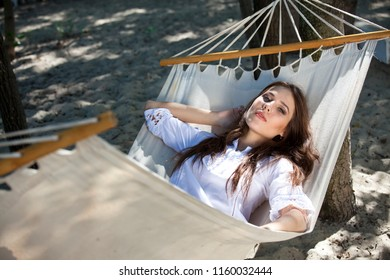 Woman in white shirt chilling on Hammock on the beach