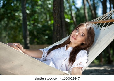 Woman in white shirt chilling on Hammock