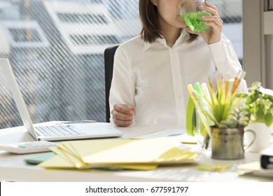 A woman with a white shirt drinks melon soda.