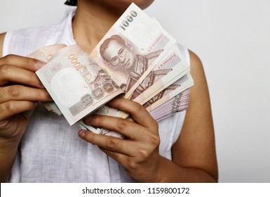 Woman in white shirt holding and counting pile of Thai Baht money in white background