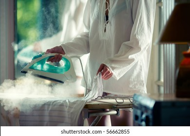 Woman in white shirt ironing and steaming the skirt
