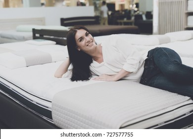 A woman in a white shirt and jeans in a mattress store. She examines the mattress she wants to buy. She lay down on the mattress and examines it.