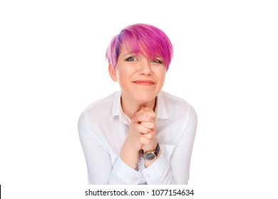 Woman in white shirt and with pink hair holding hands together and looking desperately at camera with hope asking for forgiveness isolated on white. Please, help me concept