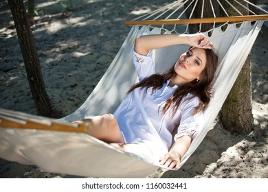 Woman in white shirt resting on Hammock in an outdoor setting