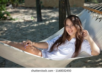 Woman in white shirt resting on Hammock