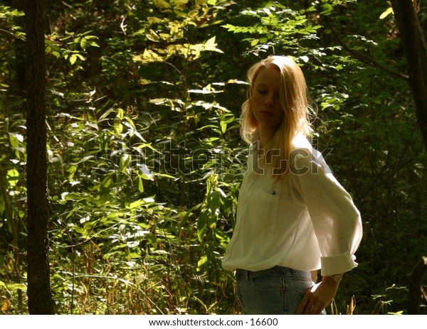 woman in white shirt silhouetted by sun.