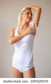 Woman in white shirt wiping the armpit with wet wipes, perspiration, sweat