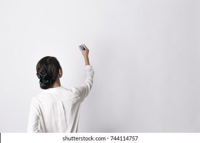 Woman in white shirt writing on imaginary screen/whiteboard with blue marker on white background. Back view. Half length portrait. Teacher/office worker.