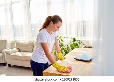 Woman in white shirt and yellow protective rubber gloves cleaning at home and wiping dust on wooden tablel with pink rag, copy space. Housework, cleanig and chores concept
