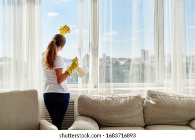 Woman in white shirt and yellow rubber gloves cleaning window with cleanser sprayer and yellow rag at home or office, copy space. People, housework and housekeeping concept
