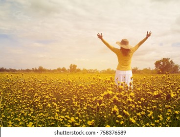 A woman in a white skirt holds her hand in a meadow full of yellow flowers. There is a sky and a forest that is as far away as the background.