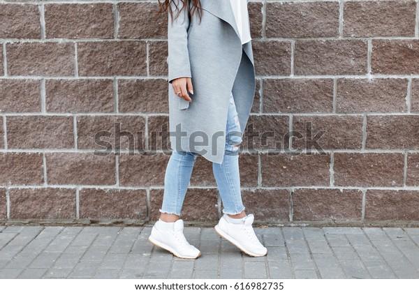 白いスニーカーと青いジーンズを身に着けた女性、レンガ壁の近くのグレーコート