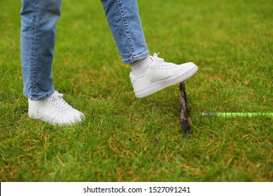 Woman in white sneakers and jeans stepping accidentally on a rake on green grass. Carelessness concept, same mistake, lifestyle. Working outdoor in garden, safety, instrument. Close up, copy space