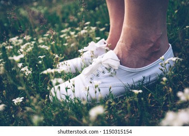 Woman in white sneakers standing on spring meadow with flowers. Feet close-up. Vintage.