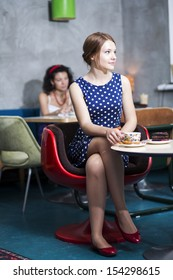 Woman in white spotted dress sit in cafe