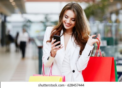 Woman in white suit doing online shopping through mobile phone. Girl in fashion look holding colorful bags near shoulder, looking at phone and smiling. Indoors, interior