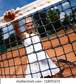 Woman in a white suit sitting on her knees and holding tennis net