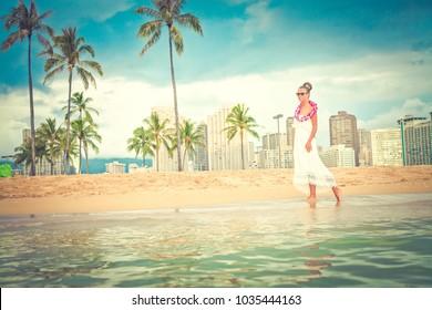 woman in white summer dress enjoying nature on the Hawaiian beach.