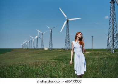 Woman in a white summer dress on a field of mills