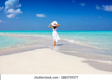 A woman in a white summer dress stands on a sandbar surrounded by turquoise ocean in the Maldives islands - Shutterstock ID 1883759377