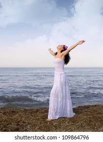 The woman in a white sundress on seacoast with open hands. Cloud sky