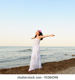 The woman in a white sundress on seacoast with open hands. A picturesque landscape