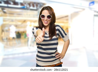Woman with white sunglasses with the thumb up. Over shopping center background