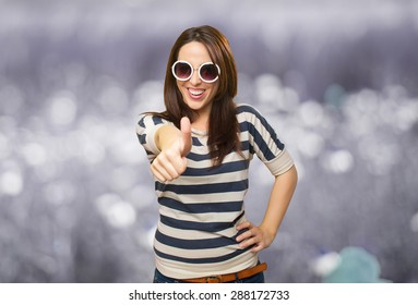 Woman with white sunglasses with the thumb up. Over abstract background