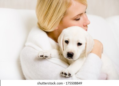 Woman in white sweater embraces Labrador puppy