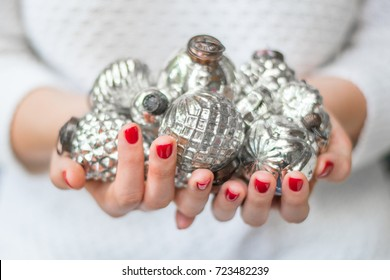 woman in white sweater holding antique silver oranments with perfect red nails symbolizing Christmas and the holidays