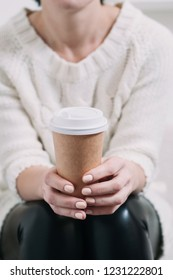 A woman in a white sweater holding a paper Cup of coffee. Template for text or design