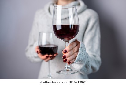 A woman in a white sweater is holding two glasses of red wine and holding out one of them. Close up.