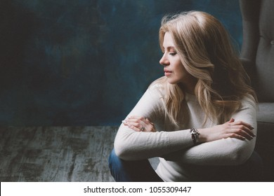 Woman in white sweater and jeans is sitting near a sofa and fold her hands and looking aside. Green background.