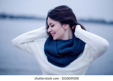Woman in a white sweater and a knitted scarf