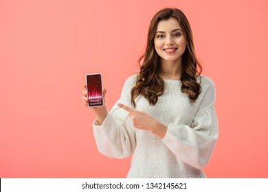 woman in white sweater pointing with finger at smartphone with trading courses app on screen isolated on pink