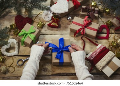 woman in a white sweater wraps a gift. The concept for the New Year and Christmas.Flat lay.