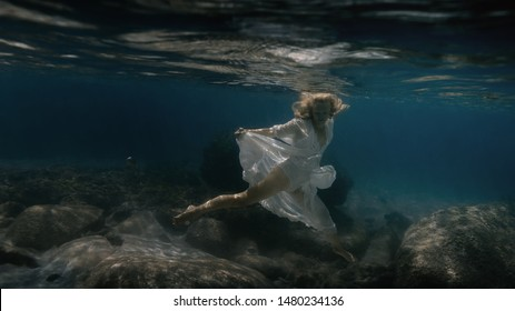 Woman in white swims underwater in the sea