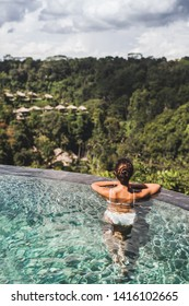 Woman in white swimsuit and sunglasses relaxing in luxury infinity pool with jungle view in Ubud, Bali