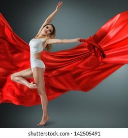 Woman in white swimwear dancing with flying fabric