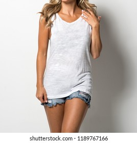 Woman in white tank top and denim shorts